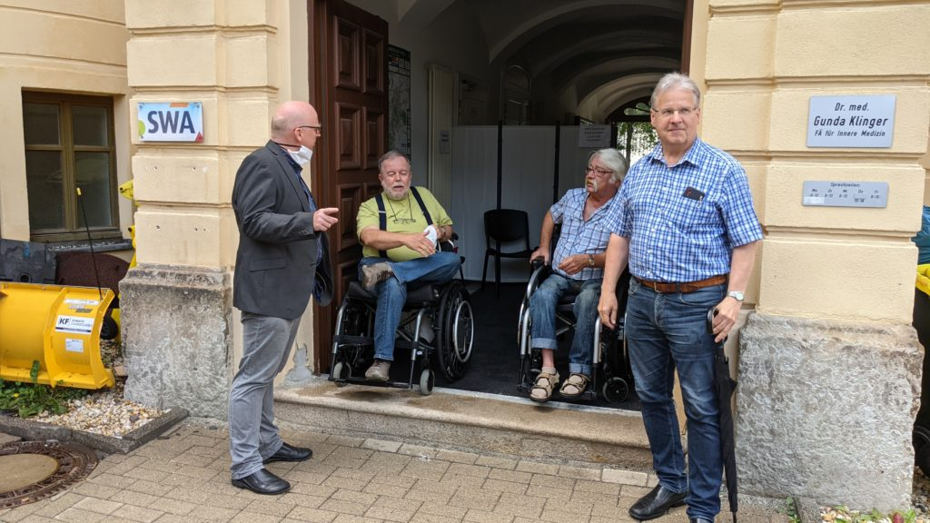 Bild mit 2 Rollifahrer und 2 Menschen im Vordergrund an der nicht barrierefreien Tür am Hinterausgang der Arzt-Praxen.